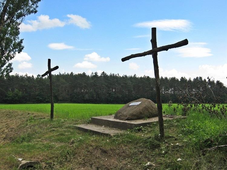 Głaz z tablica pamiątkową oraz dwa krzyże.